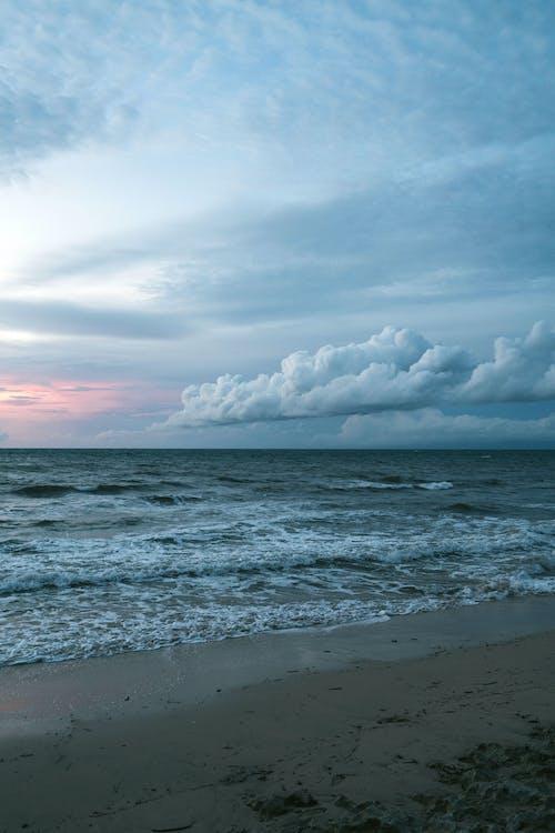 Foamy waves of sea water rippling on sandy shore in sundown in overcast