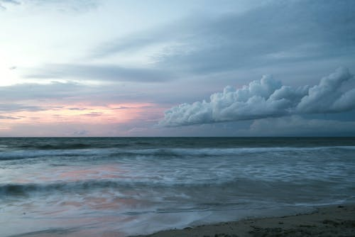 Foamy sea water waving near sandy coast in sunset in cloudy cold evening