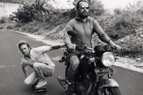 Black and white full length serious bearded biker riding motorbike with focused skater grabbing motorbike and being pulled on rural road