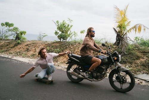 Confident skater being pulled by biker on motorcycle
