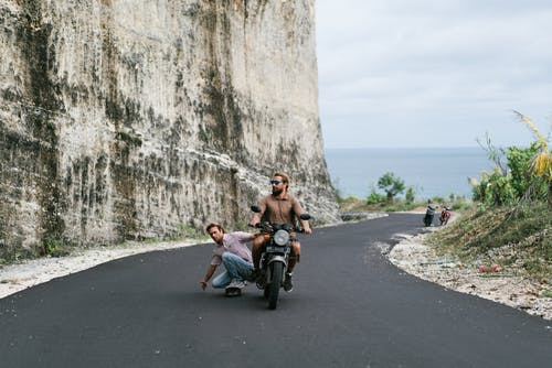 Full body man in casual wear riding skateboard while being pulled by biker on modern motorbike along asphalt road on picturesque seaside