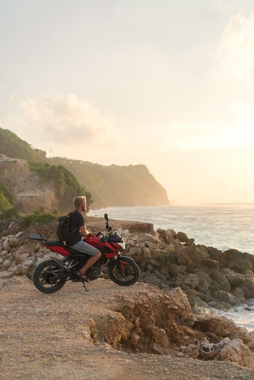 Lonely biker admiring picturesque ocean view