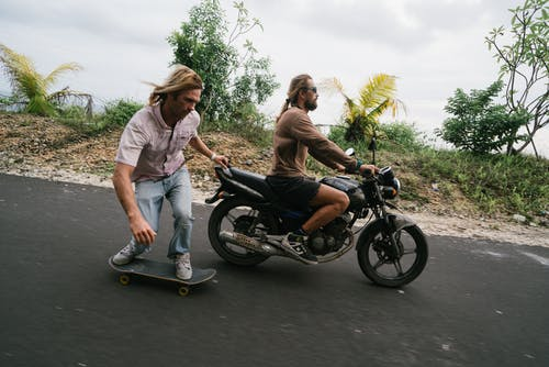 Man balancing on skateboard while being pulled by biker