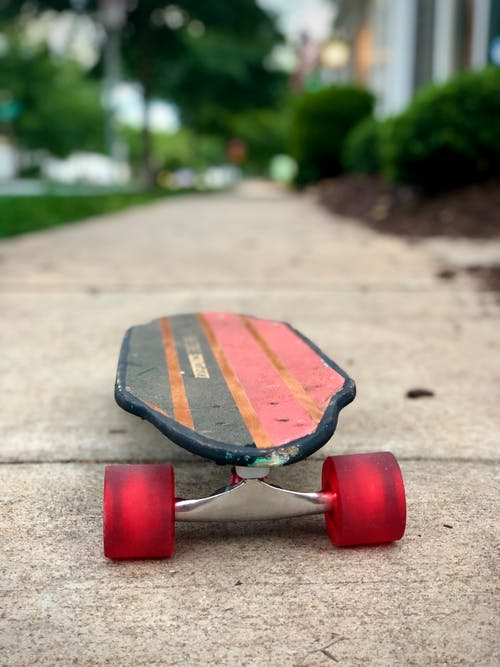 Red and Black Skateboard on Gray Concrete Floor