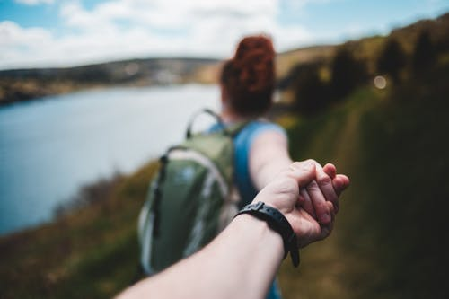 Back view of anonymous female traveler in casual clothes and backpack holding hand of crop faceless boyfriend during hiking trip in mountainous valley near lake