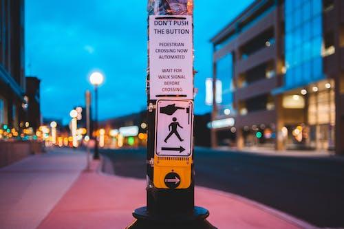 Pedestrian call button on crosswalk in contemporary city in evening