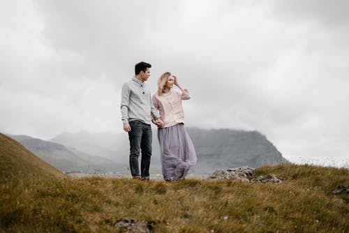 Traveling couple standing on grassy valley on hillside