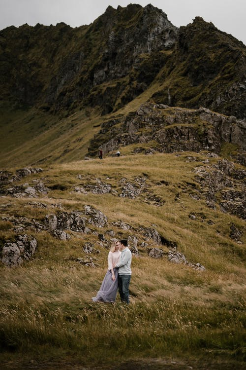 Romantic couple embracing near rocky slope