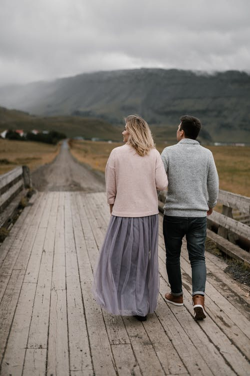 Unrecognizable couple walking on wooden path towards mountains