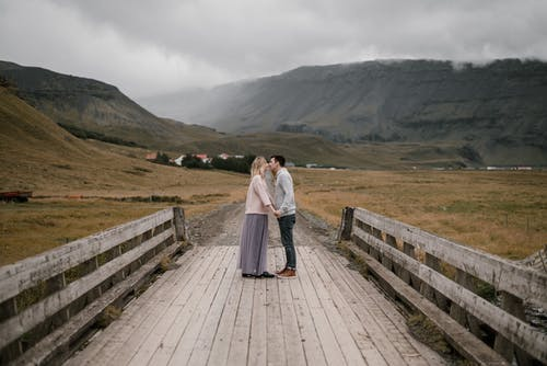Loving couple kissing on wooden path in highlands