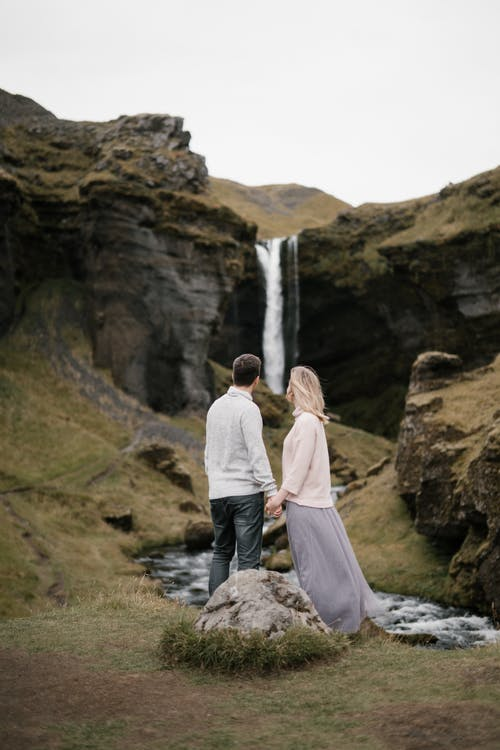 Unrecognizable young couple holding hands against picturesque waterfall