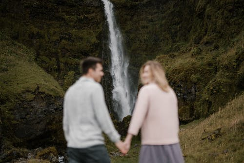 Unrecognizable young couple spending time together against waterfall