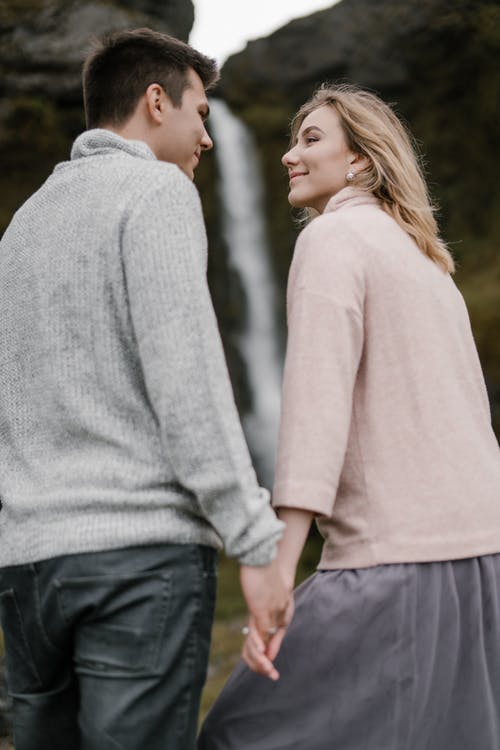 Low angle of loving young couple in casual outfits smiling and looking at each other against blurred cliff and waterfall