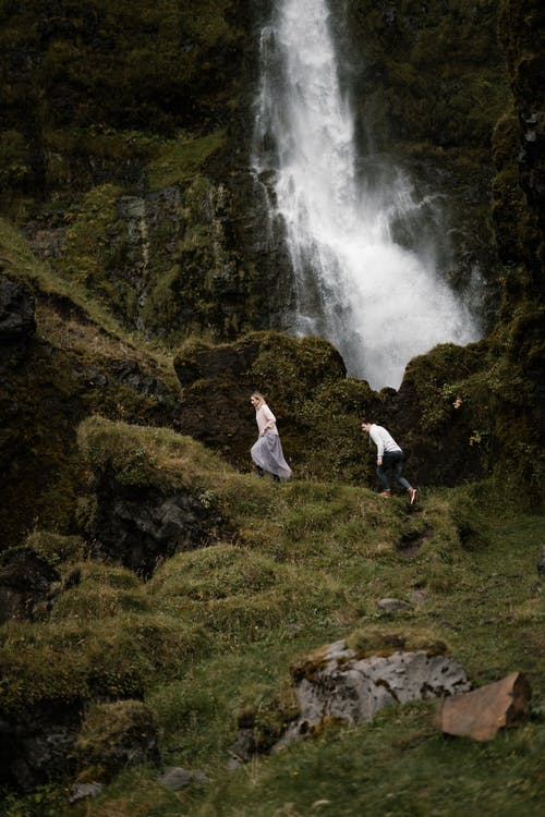 Anonymous travelers walking up rough slope towards waterfall