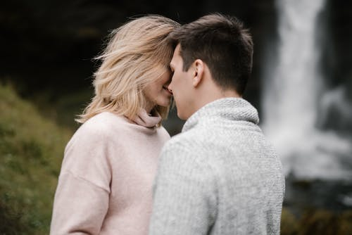 Romantic couple hugging and touching foreheads during date on nature