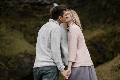Side view of happy young couple in casual outfits kissing and holding hands standing against mountain slope with flowing waterfall