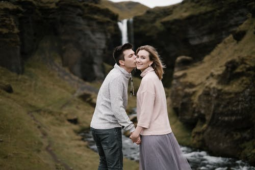 Side view of young man with closed eyes kissing beloved girlfriend on cheek while standing together against picturesque Kvernufoss waterfall in Iceland
