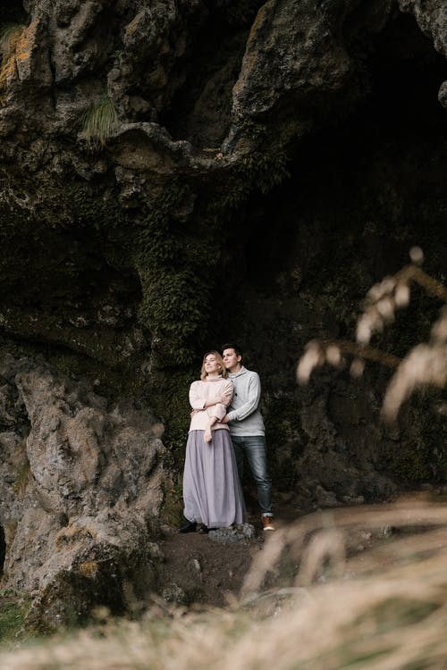 Romantic young couple cuddling near cave entrance