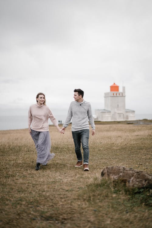 Young couple walking on grassy seashore with lighthouse in autumn