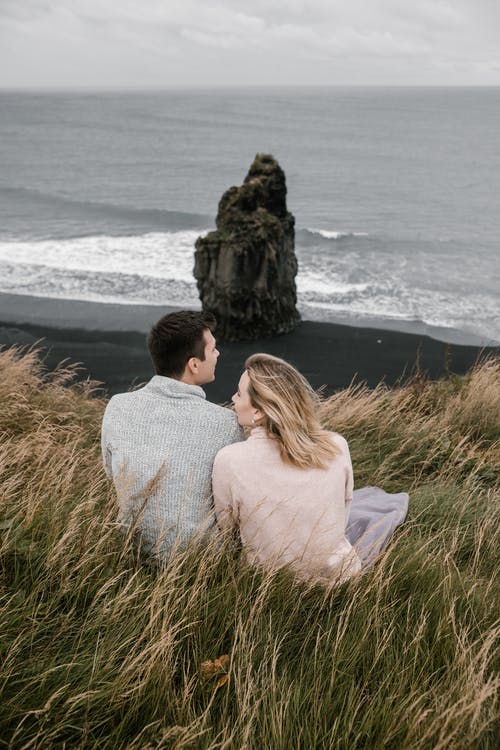 Couple sitting in grass on black sand beach in autumn