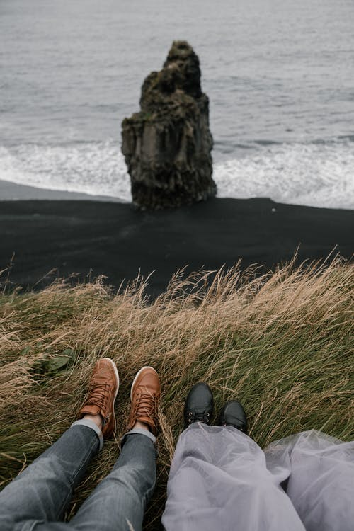 Unrecognizable couple lying in grass on Reynisfjara beach in Iceland