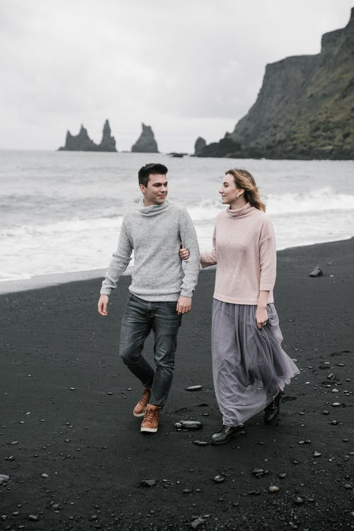 Couple walking along black sand beach with cliffs in distance