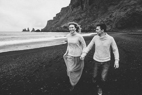 Smiling couple running along seashore holding hands