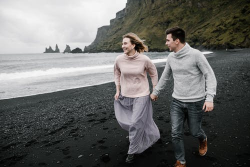 Cheerful couple running along sandy beach on cloudy day