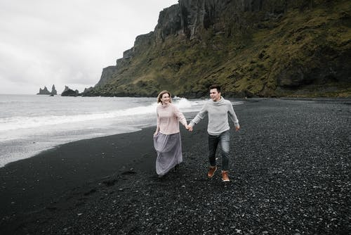 Happy loving couple holding hands and exploring magnificent black gravel beach while enjoying weekend at cliffy seacoast