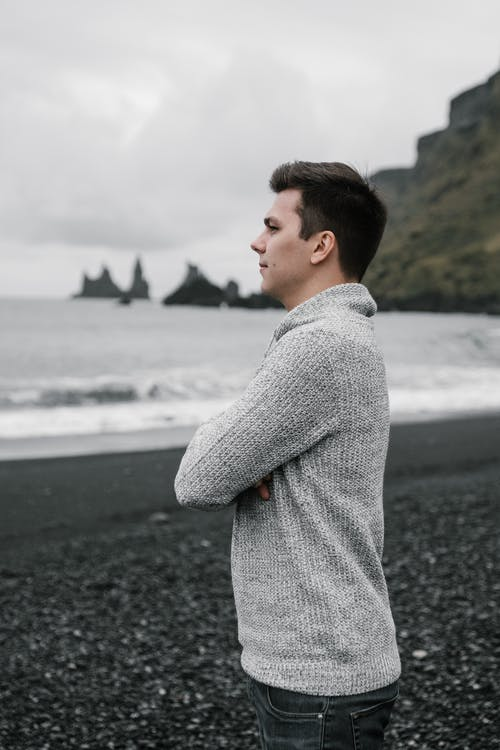 Pensive young man standing on seashore and admiring view