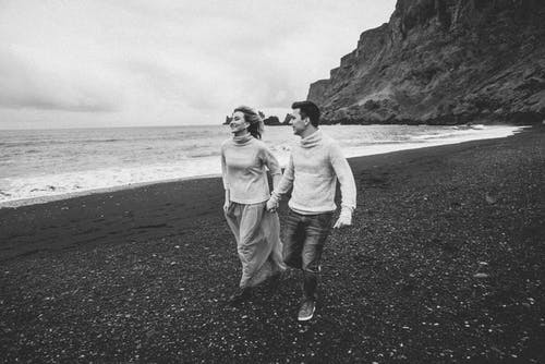 Young boyfriend and girlfriend exploring pebble beach on romantic date