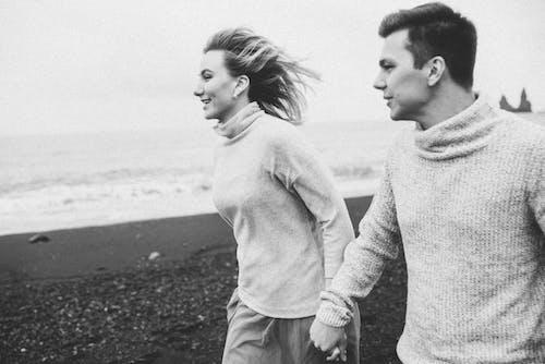 Positive married couple exploring seashore at weekend