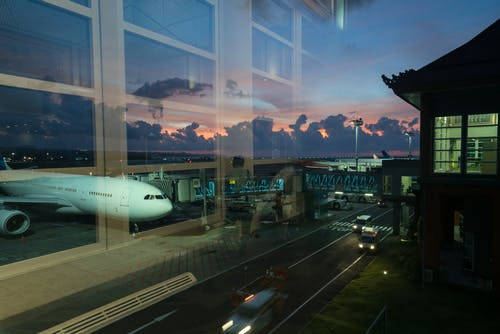 Through glass modern aircraft parked near airbridge in contemporary airport against picturesque dusk sky