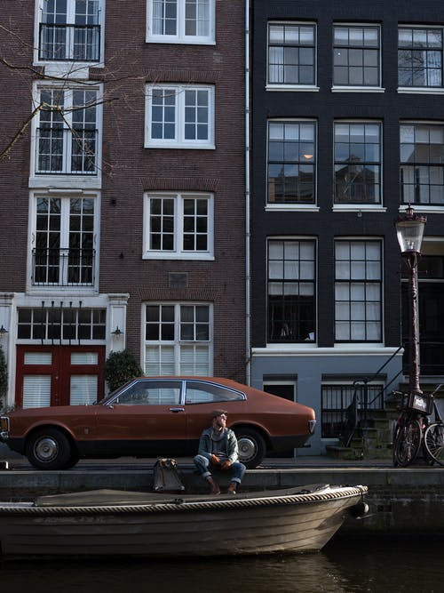 Full body anonymous male in casual clothes resting on paved riverside near city canal with boat against cozy narrow brick houses and retro car