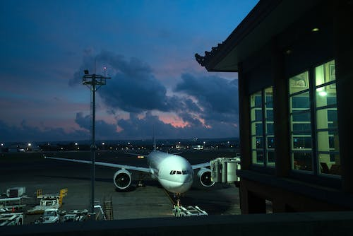 Aircraft parked near airport terminal at night