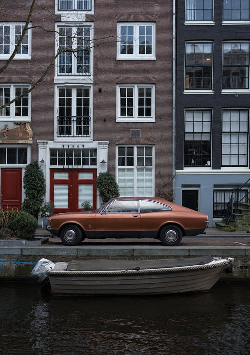 Retro car near canal with boat against narrow cozy houses