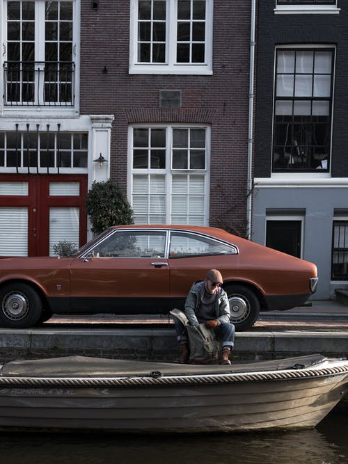 Man sitting on riverside near retro car and boat
