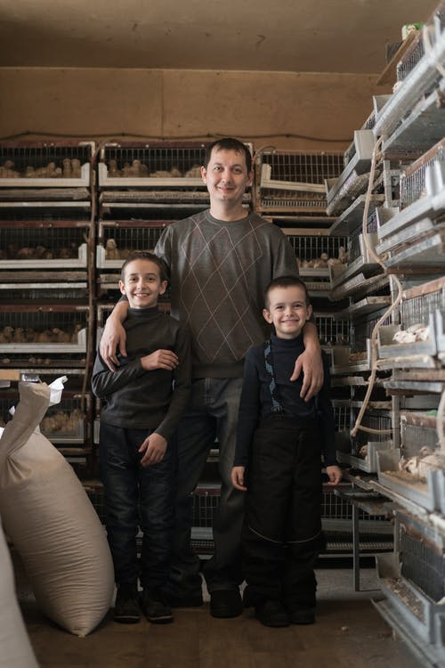 Full body of happy father and sons smiling while standing together near cages at poultry farm