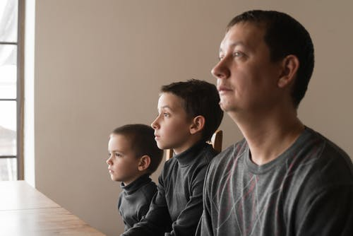 Focused young man with little sons sitting at desk