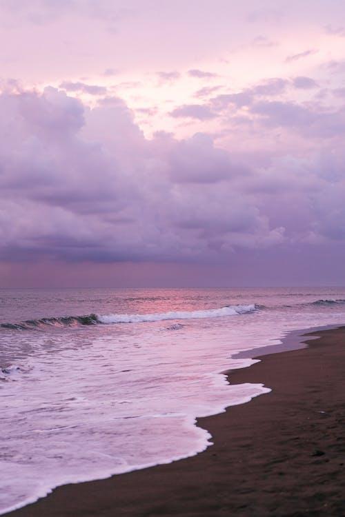 Waving sea and sandy shore against purple sky
