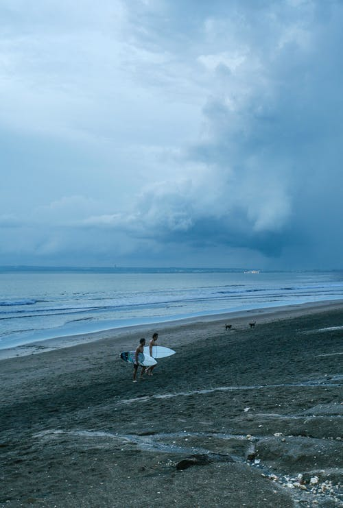 Ocean coast with surfers walking on coast and carrying surfing boards during cloudy weather