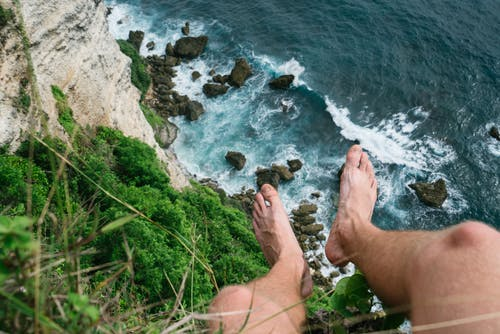 Anonymous traveler sitting on cliff high above sea