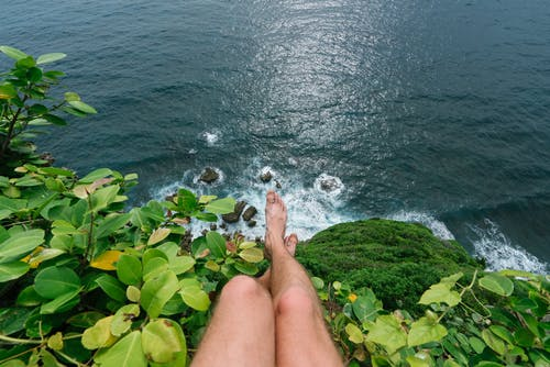 Faceless barefoot man sitting on high cliff