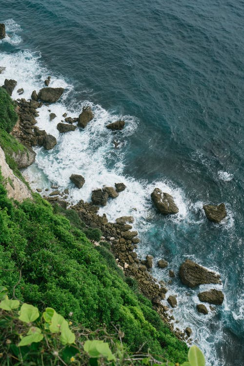 Amazing rocky seashore with moss and cliff over waving sea with turquoise water
