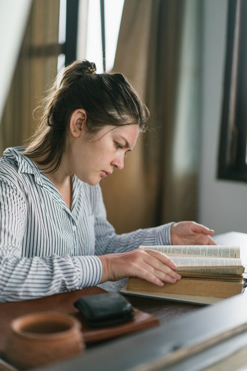 Thoughtful woman reading book sitting at table