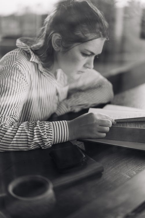Focused young woman reading book in cafe