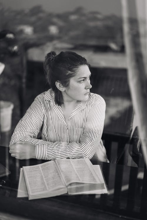 Serious young lady with thick book looking away