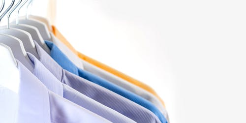 Hangers with collection of various classic shirts placed in row on rack against white background