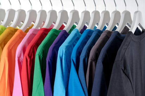 Row of multicolored similar clothes on hangers