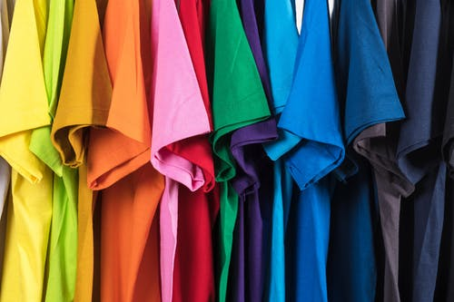 Set of multicolored t shirts hanging in row